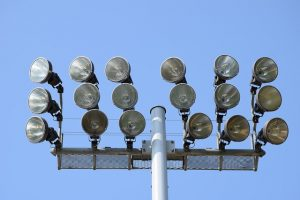 Industrial outdoor lights against a blue sky.